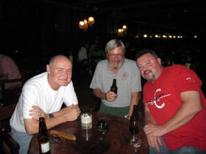 Gomez enjoying a few beers with his son Rich, right, and Professor Larry Davenport of Samford University, in a jungle honky-tonk near Iquitos, Peru